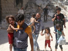 Children are carried amid the rubble of destroyed buildings