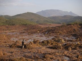 A man walks following a mudslide after a dam owned by Vale SA and BHP Billiton Ltd burst in Mariana