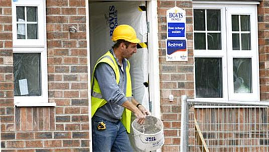A builder works at a Bovis homes housing development near Bolton