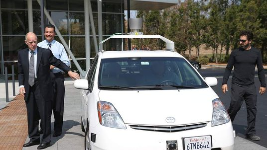 California Gov. Jerry Brown and Google co-founder Sergey Brin exit a self-driving car