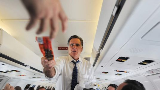 Romney hands out beef jerky to journalists on board his campaign plane at the Philadelphia International Airport, September 28