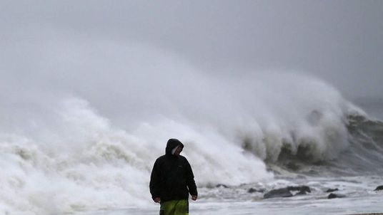 A man stands on the beach as heavy surf from Hurricane Sandy pound the shoreline in Cape May, New Jersey.