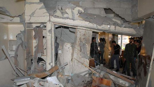 Syrian security members inspect the damage in a building, caused by an explosion near the Dama Rose hotel in Damascus