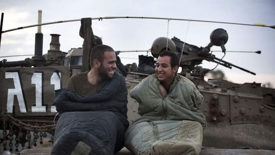 Israeli soldiers wake up on top of their tank at an army deployment area
