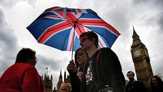 A couple carry a Union Flag umbrella as they walk in the rain along Westminster Bridge in London