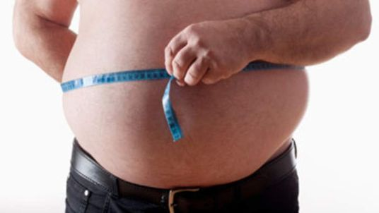 A fat man measuring his stomach with a tape measure