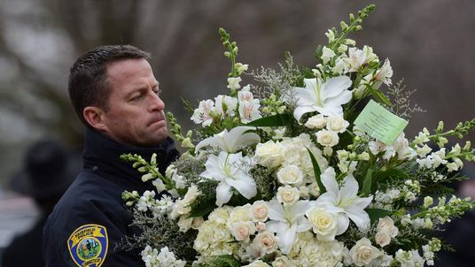 A police officer carries a bouquet of flowers for Noah Pozner