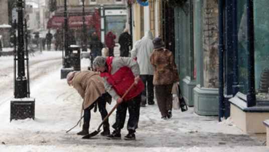 Shopkeepers try and clear the snow as people brave the conditions on Wells' main shopping street.