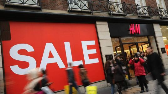 Shoppers make their way past a sale sign