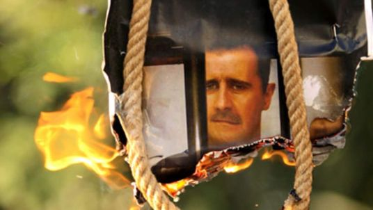 A makeshift gallows with a poster shows president Bashar al-Assad as temperatures rise in Syria