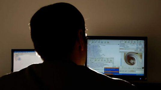 Man sits at blurred computer screen