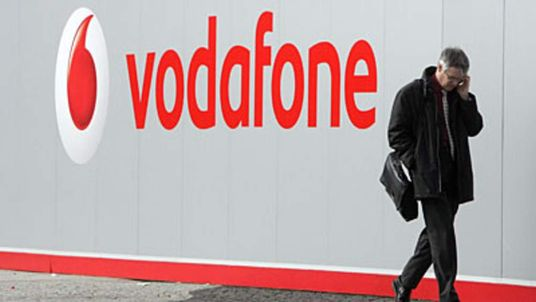 A man walks past a Vodafone sign