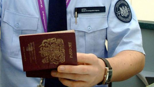 An immigration officer checking a passport at Terminal 1 at Heathrow Airport