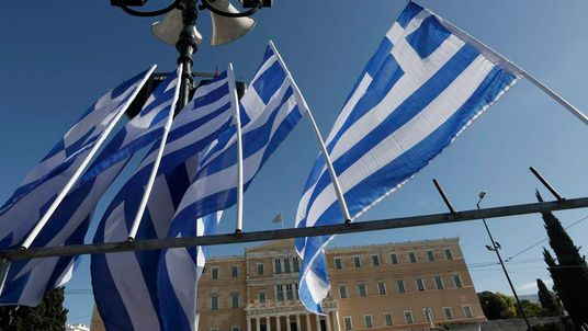 Greek flags fly in front of the parliament building during a rally in central Athens