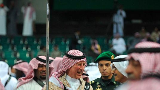 Britain's Prince Charles, wearing a traditional Saudi attire, dances with a sword during the a traditional Saudi dancing, known as 'arda', in Riyadh