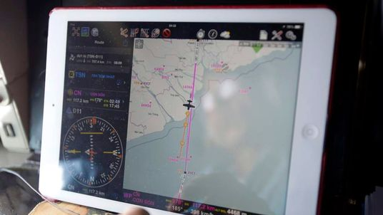 Military officer Dong is seen reflected in a map on an iPad showing path of Vietnam Air Force search and rescue aircraft that he is travelling on, during a mission to find Malaysia Airlines flight MH370 that disappeared, off Con Dao island