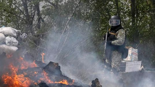 A Ukrainian security force officer is deployed at a checkpoint set on fire and left by pro-Russian separatists near Slaviansk