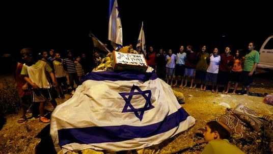 Israelis protest at a junction near the West Bank city of Hebron, after Israeli forces found the bodies of three missing teenagers