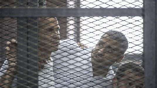 Australian journalist Peter Greste (L) and his colleagues, Egyptian-Canadian Mohamed Fadel Fahmy (C) and Egyptian Baher Mohamed