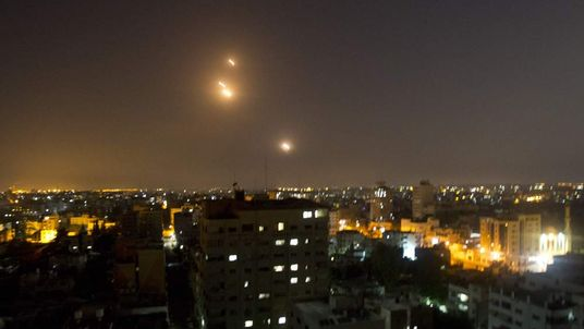 A picture taken from Gaza city shows a long-range J-80 rocket being launched from the Gaza strip towards Israel.
