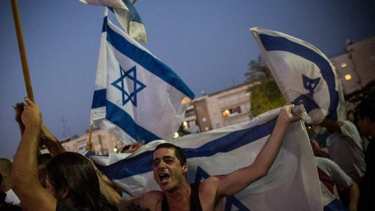 A right-wing supporter of Israel holds up a flag