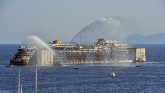 The stricken cruise ship Costa Concordia is towed away