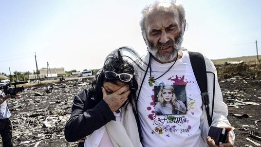 Angela Rudhart-Dyczynski and Jerzy Dyczynski from Australia react as they arrive on July 26, 2014 at the crash site of the Malaysia Airlines Flight MH17
