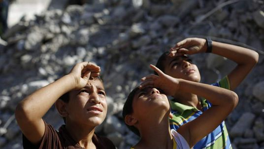 Palestinian children look up at an Israeli plane in Beit Lahia in the northern Gaza Strip