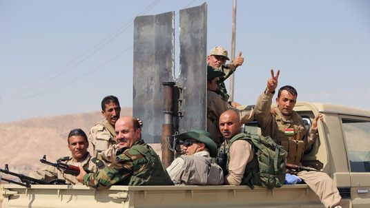 Iraqi Kurdish Peshmerga fighters on the back of a truck as they head to the Mosul dam