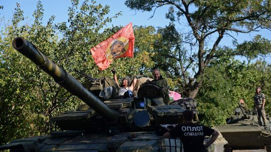 Pro-Russian fighters sit ontop of a tank in Starobesheve, southeast of Donetsk