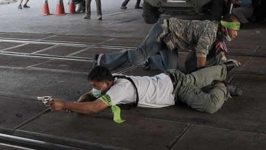 A Thai pro-election protester takes cover and aims his gun before shooting towards Thai anti-government protesters in Bangkok.