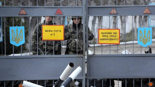 Ukrainian marines guard the gates of their base in the eastern Crimea port city of Feodosiya