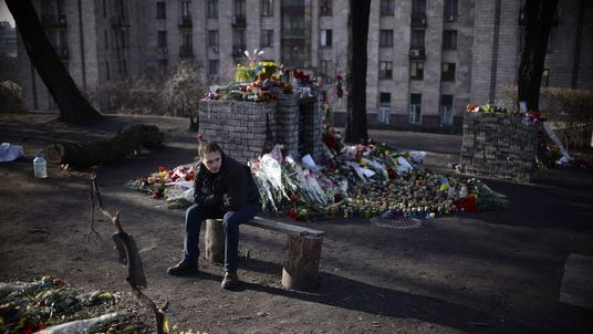 A man sits next to a makeshift shrine of the fallen in Kiev.