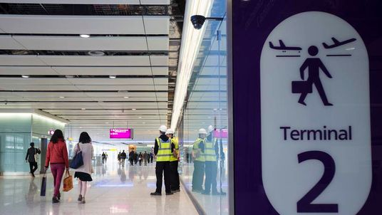 People walk in the under-construction interior of Heathrow airport's new Terminal 2.