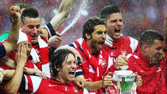 Tomas Rosicky of Arsenal leads the trophy celebrations after the FA Cup with Budweiser Final match between Arsenal and Hull City at Wembley Stadium.