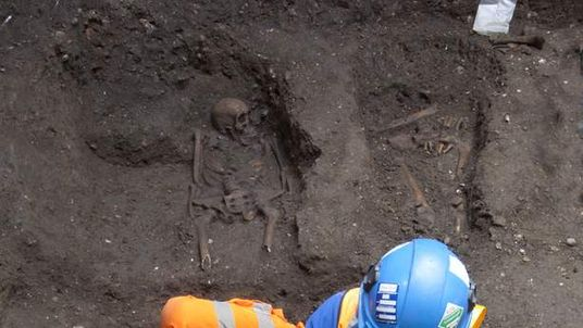 An archaeologist examines remains found during construction of the Crossrail project