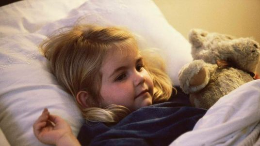 Close-up of a girl lying on the bed with her teddy bear