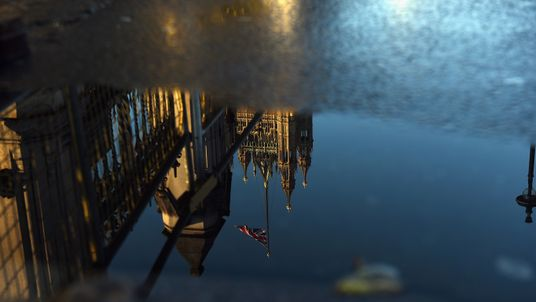 The Houses of Parliament are reflected in a  puddle