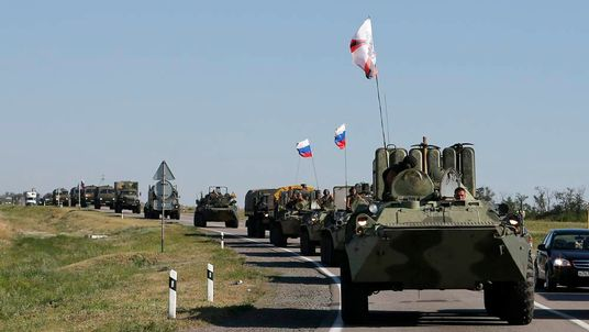 Russian military personnel ride atop APCs outside Kamensk-Shakhtinsky