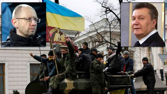 Anti-Yanukovich protesters wave a Ukranian flag atop a Ukranian Army Armoured Personnel Carrier (APC) outside the parliament building in Kiev