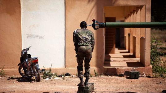 A French soldier peers into the barrel of a tank at a Malian air base in Bamako