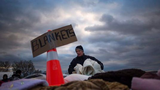 A victim of superstorm Sandy takes blankets from a aid distribution site in Staten Island