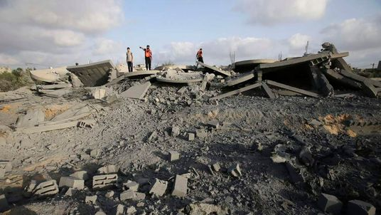Palestinian members of the civil defence survey the rubble of a house which police said was destroyed in an Israeli air strike in Rafah, in the southern Gaza Strip