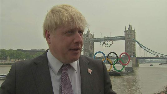 London Mayor Boris Johnson stands with the Olympic Rings and Tower Bridge in the background