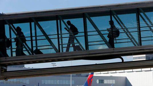 Passengers pull trolleys as they board an aircraft at Brussels International Airport