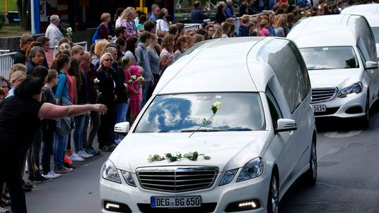 People throw flowers on hearses carrying coffins with remains of victims of the Germanwings flight 4U 9525 plane disaster as they drive past the Joseph-Koenig-Gymnasium high school in Haltern am See
