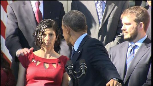 President Obama helps a woman who was feeling faint during his healthcare speech