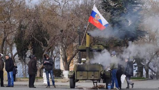 Protesters raise a Russian flag in Crimea, Ukraine