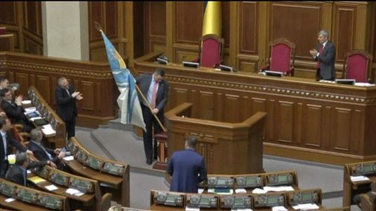 Ukrainian boxer-turned-politician Vitaly Klitschko carries a Ukrainian Navy flag into parliament to show support for the country's troops in Crimea as tensions with Russia grow