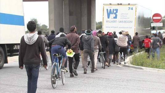 Refugees follow an aid truck.